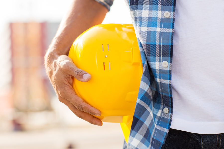 Construction worker holding helmet during National Safety Month