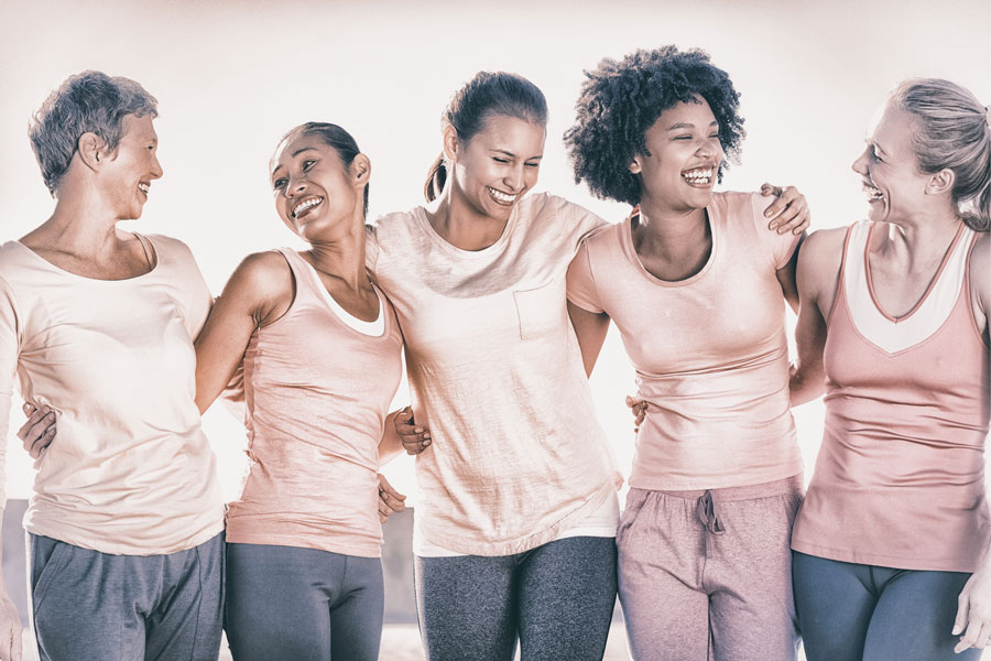 5 women smiling during Breast Cancer Awareness Month