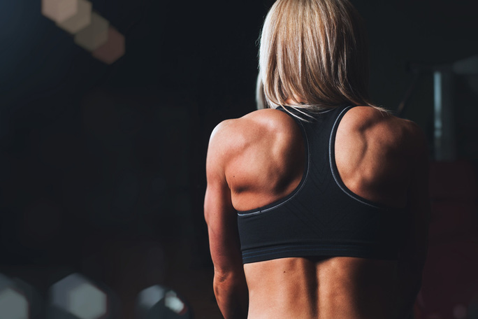 women's muscular back shown in gym